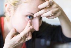 La muchacha pone las lentes de ojo Foco en la lente Fotos de archivo