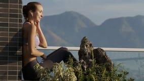 La muchacha pone los auriculares en terraza por las plantas de tiesto