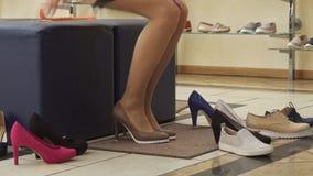La muchacha pone los zapatos marrones en la tienda almacen de metraje de vídeo