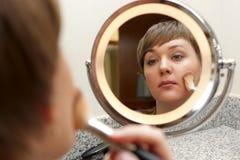 La muchacha pone maquillaje fotografía de archivo