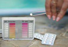 La muchacha pone un probador de la tableta para probar el pH y el cloro Foto de archivo