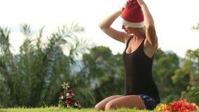 La muchacha pone un sombrero de la Navidad almacen de metraje de vídeo