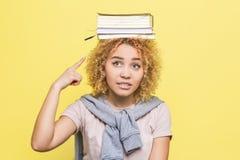 La muchacha ponting en el libro que está en su cabeza La frustran El ` t del doesn de la muchacha conoce qué hacer con él Imagen de archivo