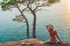La muchacha por el mar en la puesta del sol y el sombrero lleva a cabo las manos Imagenes de archivo
