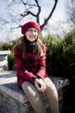 La muchacha positiva de la edad de escuela está en el parque Fotos de archivo libres de regalías