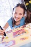 La muchacha positiva de la escuela está pintando en el país Fotografía de archivo libre de regalías