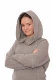 La muchacha positiva está en sudadera con capucha gris. Fotografía de archivo