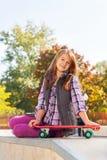 La muchacha positiva sostiene el monopatín se sienta en la tierra Imagen de archivo