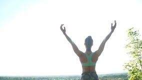 La muchacha practica yoga al aire libre en un clifftop increíble Cámara lenta almacen de video