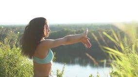 La muchacha practica yoga al aire libre en un clifftop increíble Cámara lenta metrajes