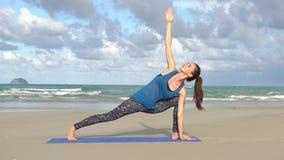 La muchacha practica yoga cerca del océano, mar metrajes