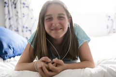 La muchacha pre adolescente es relajante en la cama y escuchar la música con los auriculares Fotos de archivo