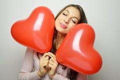 La muchacha preciosa con los ojos y el corazón cerrados de la tarjeta del día de San Valentín hincha en sus manos Mujer joven dul Fotos de archivo libres de regalías