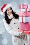 La muchacha preciosa en abrigo de invierno consigue las cajas de regalo de la Navidad Fotos de archivo
