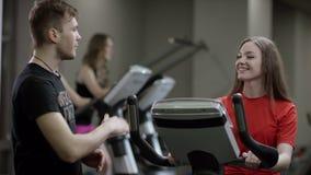 La muchacha preciosa en camisa roja trabaja vigoroso en la bicicleta estática y el instructor viene avaricia ella en el nuevo gim metrajes