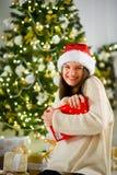 La muchacha preciosa en casquillo del ` s de Papá Noel presiona a sí misma una caja con el regalo de la Navidad Imagen de archivo libre de regalías