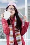 La muchacha preciosa en ropa caliente disfruta de la bebida caliente Fotografía de archivo