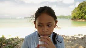La muchacha preciosa es agua potable con la paja de la taza plástica almacen de metraje de vídeo