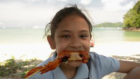 La muchacha preciosa está comiendo el pollo asado a la parrilla en la playa almacen de metraje de vídeo