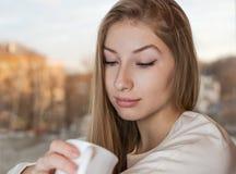 La muchacha preciosa está disfrutando del aroma de una taza Imagen de archivo