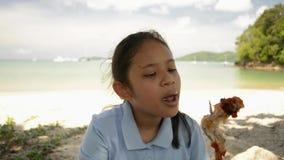 La muchacha preciosa est? comiendo el pollo asado a la parrilla en la playa almacen de video