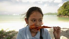 La muchacha preciosa est? comiendo el pollo asado a la parrilla en la playa metrajes