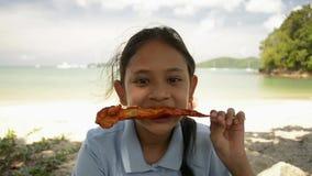 La muchacha preciosa est? comiendo el pollo asado a la parrilla en la playa almacen de metraje de vídeo