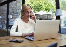 La muchacha preciosa vistió elegante sentarse en el café de consumición del café acogedor brillante y hablar en el teléfono imagen de archivo