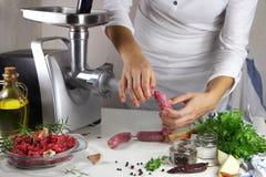 La muchacha prepara las salchichas hechas en casa Imagen de archivo libre de regalías