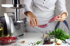 La muchacha prepara las salchichas hechas en casa Imagenes de archivo