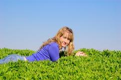 La muchacha puesta en una hierba Imágenes de archivo libres de regalías
