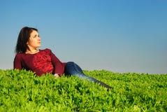 La muchacha puesta en una hierba Fotografía de archivo libre de regalías