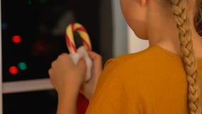 La muchacha puso el bastón de caramelo en calcetín de la Navidad, adornando la casa, preparándose para el día de fiesta almacen de video