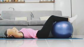 La muchacha puso sus pies en la bola que hacía los diversos ejercicios de los deportes para la prensa