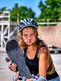La muchacha que anda en monopatín adolescente útil y agresiva mantiene su monopatín al aire libre Imagen de archivo