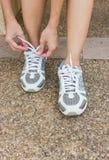 La muchacha que ata las zapatillas deportivas. imágenes de archivo libres de regalías