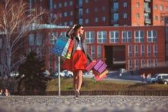 La muchacha que camina con compras en las calles de la ciudad Fotografía de archivo libre de regalías