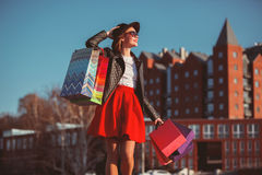 La muchacha que camina con compras en las calles de la ciudad Fotos de archivo libres de regalías