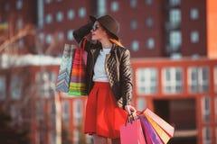 La muchacha que camina con compras en las calles de la ciudad Imagen de archivo libre de regalías