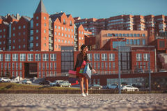 La muchacha que camina con compras en las calles de la ciudad Fotos de archivo