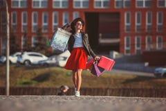 La muchacha que camina con compras en las calles de la ciudad Imagenes de archivo