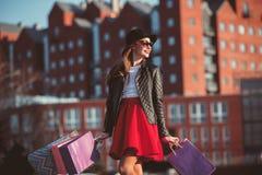 La muchacha que camina con compras en las calles de la ciudad Foto de archivo libre de regalías