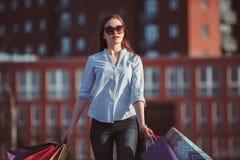 La muchacha que camina con compras en las calles de la ciudad Imagen de archivo