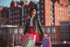 La muchacha que camina con compras en las calles de la ciudad Fotografía de archivo