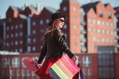 La muchacha que camina con compras en las calles de la ciudad Foto de archivo