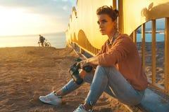 La muchacha que camina hermosa joven se sienta en la playa y disfruta de vista a Imagen de archivo libre de regalías