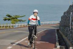 La muchacha que completa un ciclo cuesta arriba en el camino Fotos de archivo