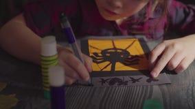 La muchacha que dibuja algo en una tarjeta Preparación para la celebración de Halloween almacen de video