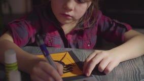 La muchacha que dibuja algo en una tarjeta Preparación para la celebración de Halloween metrajes