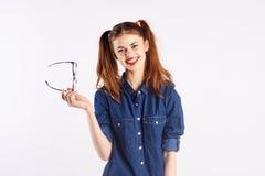 La muchacha que el adolescente en blanco aisló el fondo sostiene los vidrios, sonrisa Imagen de archivo libre de regalías